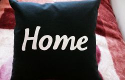 Czarne poduszki z napisami.