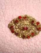 złota broszka z czerwonymi kamykami