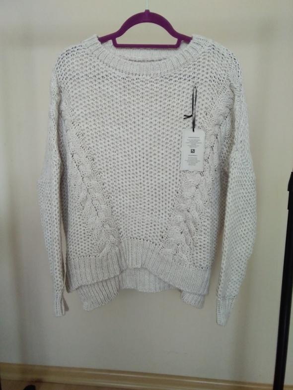Beżowy sweter warkocze