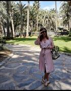 Pudrowa sukienka między palmami