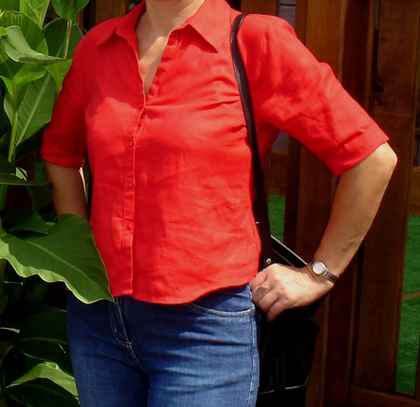 Czerwona lniana koszula z okrągło zakończonym dołem...