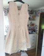 Rozkloszowana sukienka ecru połyskujący deseń...