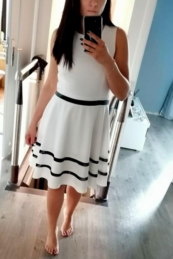 piękna biała rozkloszowana sukienka z czarnymi wstawkami...
