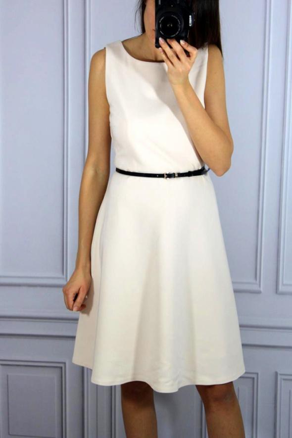 Pudrowa rozkloszowana sukienka z paskiem