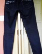 Sliczne jeansy z cwiekami na tylnych kieszeniach