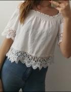 Krótka biała bluzka zdobiona haftowaną koronką na ramiączkach...