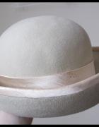 Beżowy kapelusz damski zdobiony tasiemką...