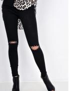 czarne spodnie z dziurami na kolanach