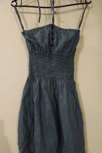 Zwiewna niebieska sukienka wiązana na szyi z czarnymi guziczkami guziki