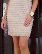 Połyskująca sukienka z falbanek i złota biżuteria