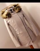 Beżowy płaszcz z kapturem zapinany na zamek