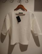 biała bluzka z tłozonego materiału
