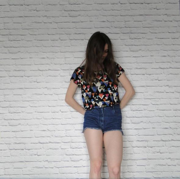 Krótsza bluza w geometryczne wzory z guzikami zapi
