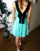 rozkloszowana zielona sukienka z kokardą i wycięciem na plecach