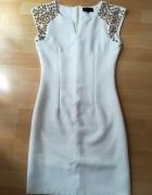 Kremowa sukienka z bogatym zdobieniem na ramionach...