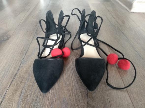 Nieużywane wiązane buty z czerwonymi pomponami