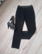 Eleganckie czarne spodnie z brązowym pasem...