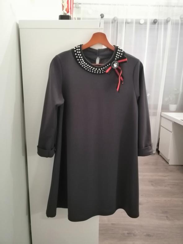 szara sukiena z ozdoba przy szyi...