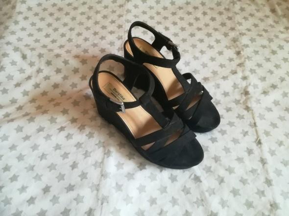 Czarne sandały na koturnie Bershka...