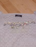 szary krótki sweterek z ozdobami z przodu...
