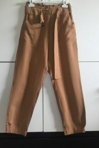 Materiałowe beżowe luźne spodnie ze ściągaczami przy kostkach...