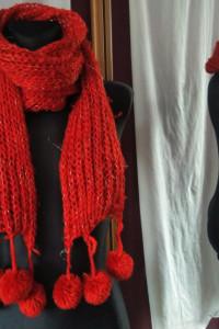 Czerwony szalik z pomponami przeplatany błyszczącą nitką...